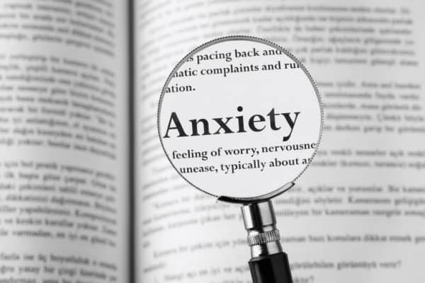 Magnifying glass highlighting the symptoms of anxiety; worry, nervous, unease